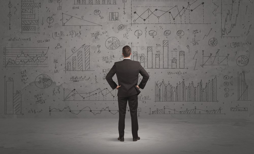 A successful confident businessman thinking about decisions, standing in front of wall full with graph pie charts and calculations concept