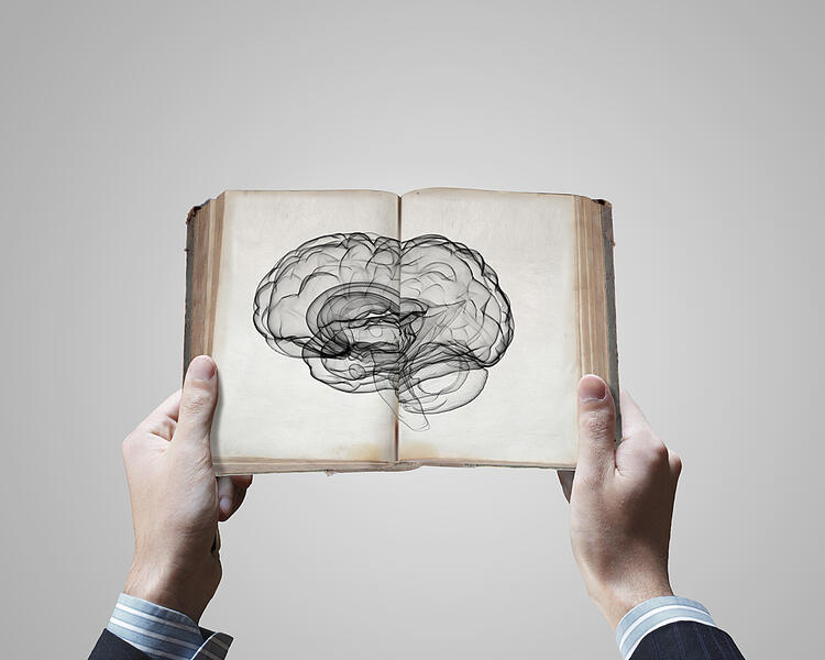SEO for beginners   SEO glossary   man holding book with brain sketch